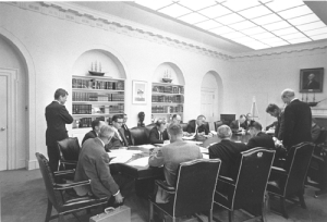 Narada prezydenta Kennedy'ego (pochylony nad stołem) z doradcami [Public domain], via Wikimedia Commons